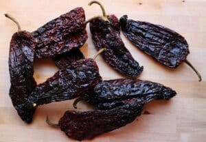 Dried chile ancho on a wooden surface.