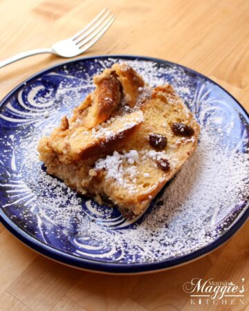 Conchas Bread Pudding on a blue plate with a fork on the side.