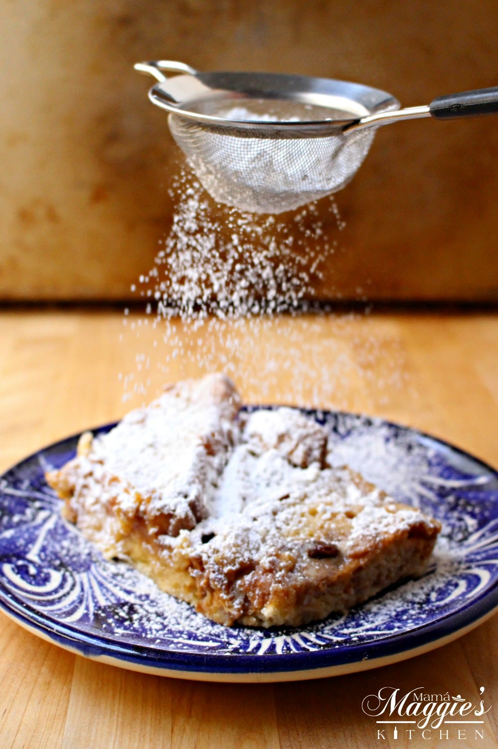 Powdered sugar sprinkling over the Conchas Bread Pudding Capirotada de Conchas. By Mama Maggie's Kitchen