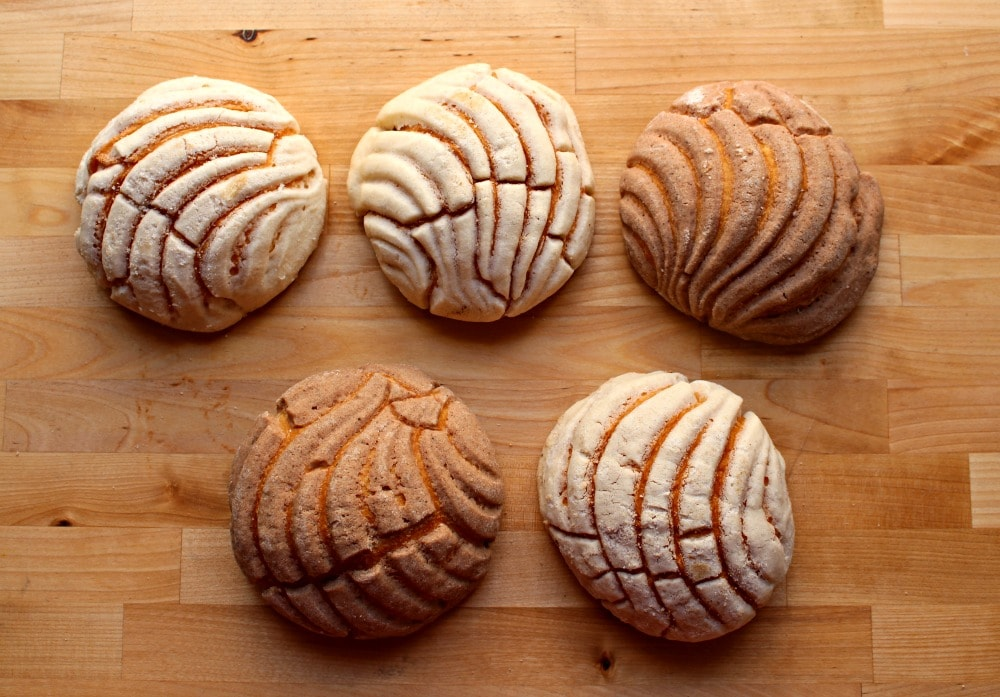 Five conchas (Mexican sweet bread) on a wooden surface.