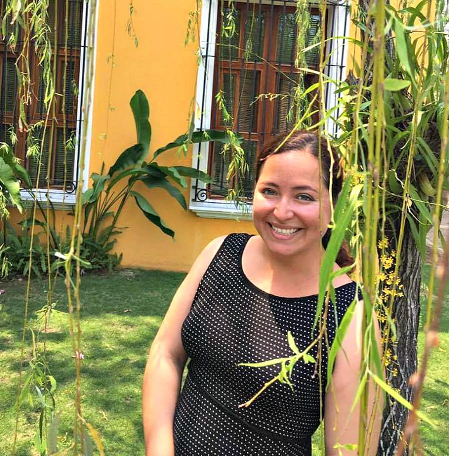 Maggie Unzueta in front of a yellow house in Tabasco, Mexico.