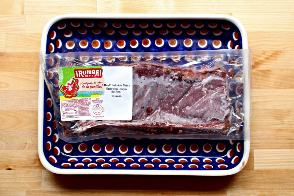 Beef still in its wrapper on a blue plate.