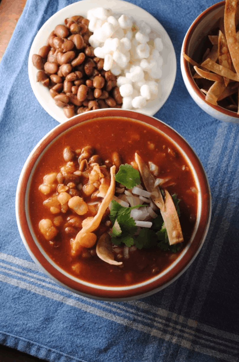Pozole de Frijol served in a bowl on a blue towel.