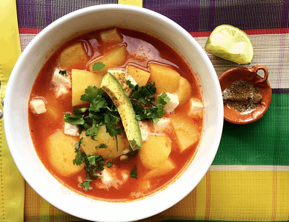 Sopa de Papa in a white bowl topped with avocado on a colorful placemat.
