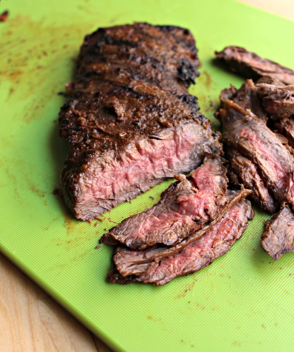 Sliced skirt steak on a green cutting board.