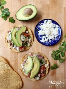Tostada de Atún on a wooden surface surrounded by avocado, cilantro, and a decorative blue plate.