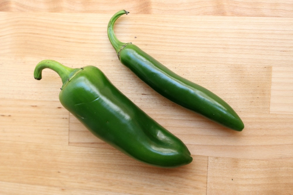 A green jalapeno Pepper next to a serrano pepper