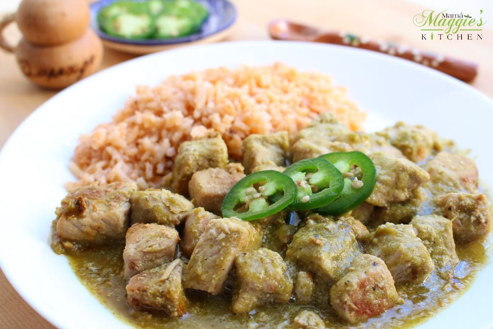 Authentic pork chile verde on a plate topped with slices of jalapeno and served next to Mexican rice.