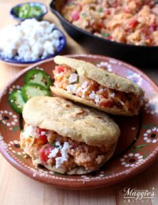 Two breakfast gorditas on a decorative Mexican clay plate.