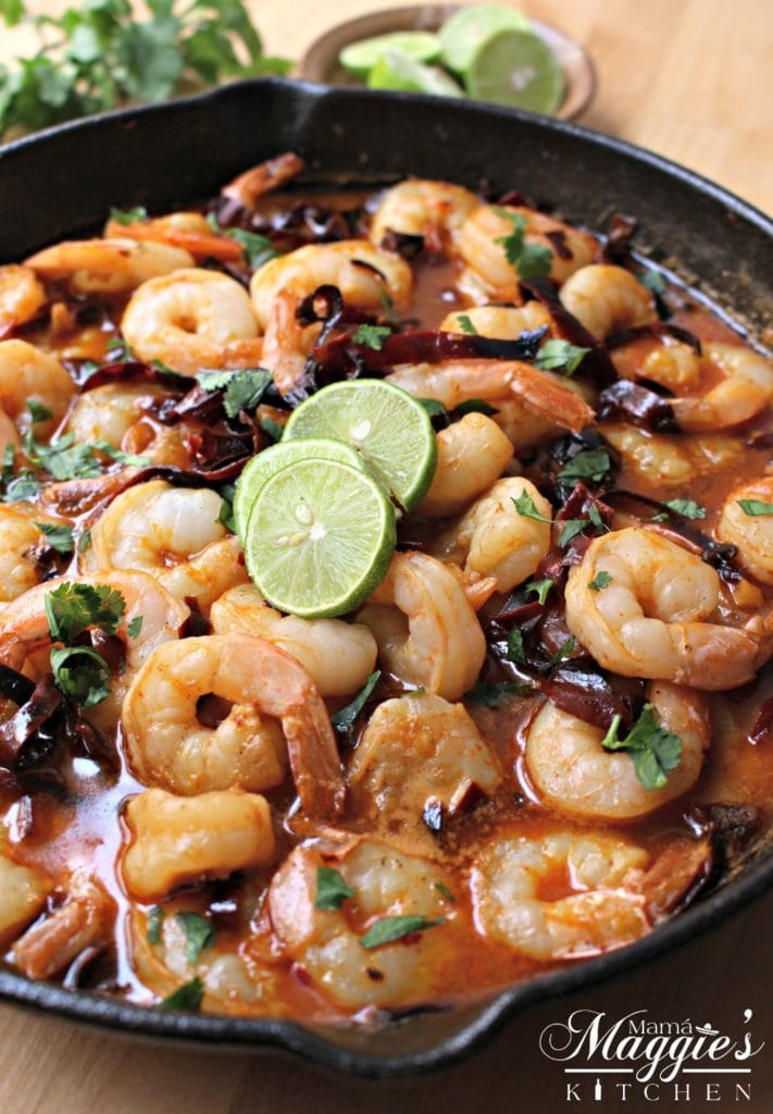 Camarones al Ajillo (Mexican Shrimp in a Spicy Garlic Sauce) in a skillet topped with lime slices.