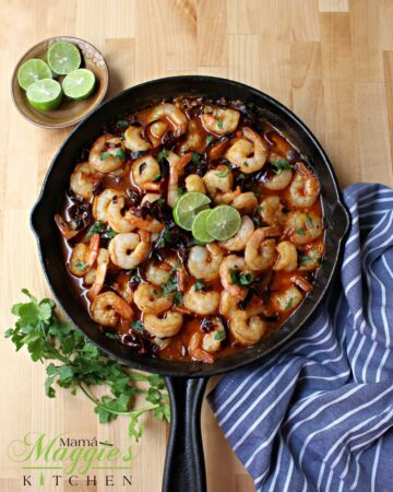 Camarones al Ajillo (Mexican Shrimp in a spicy garlic sauce) in a black iron skillet topped with lime slices and surrounded by green cilantro leaves.