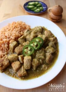 Pork Chile Verde on a white plate next to Mexican rice.