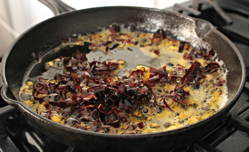 Chile de arbol and chile guajillo cooking in butter in a skillet.