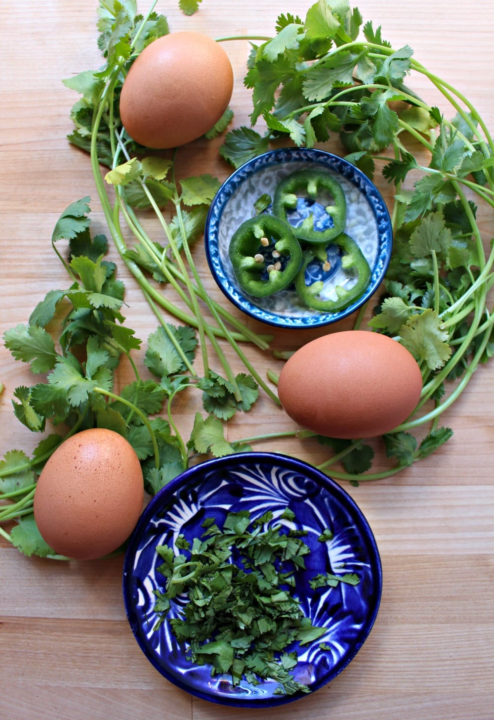 Cilantro leaves decorating a table with eggs and other toppings for the dish.