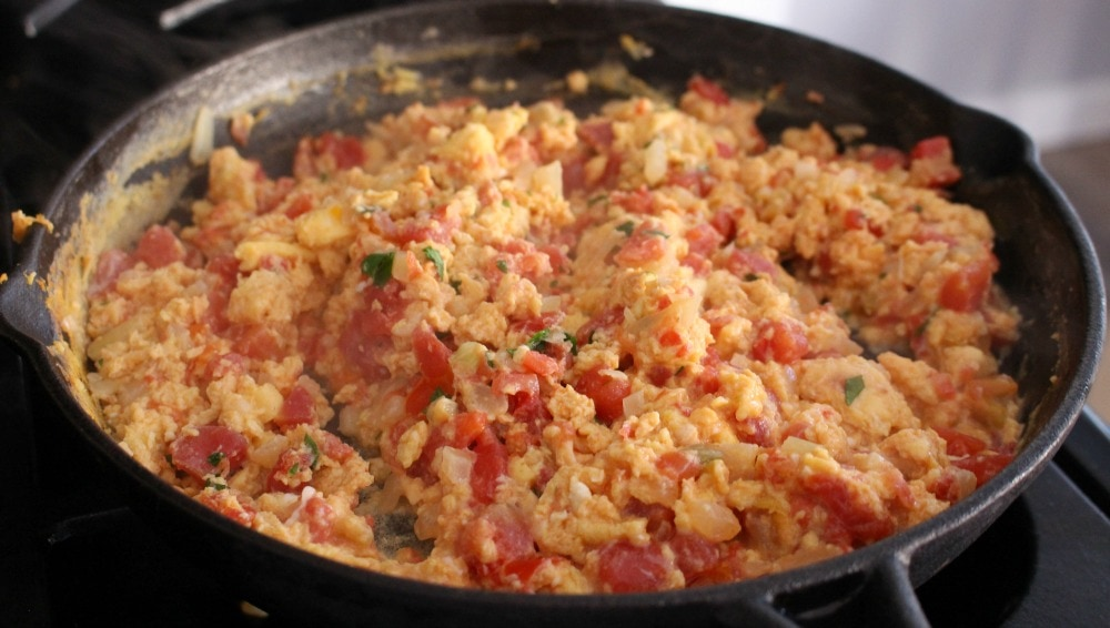 Eggs and tomatoes cooking in a black iron skillet.