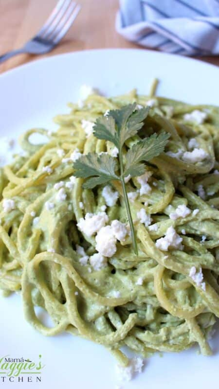 Espagueti Verde on a white plate topped with a cilantro leaf and crumbled cheese.
