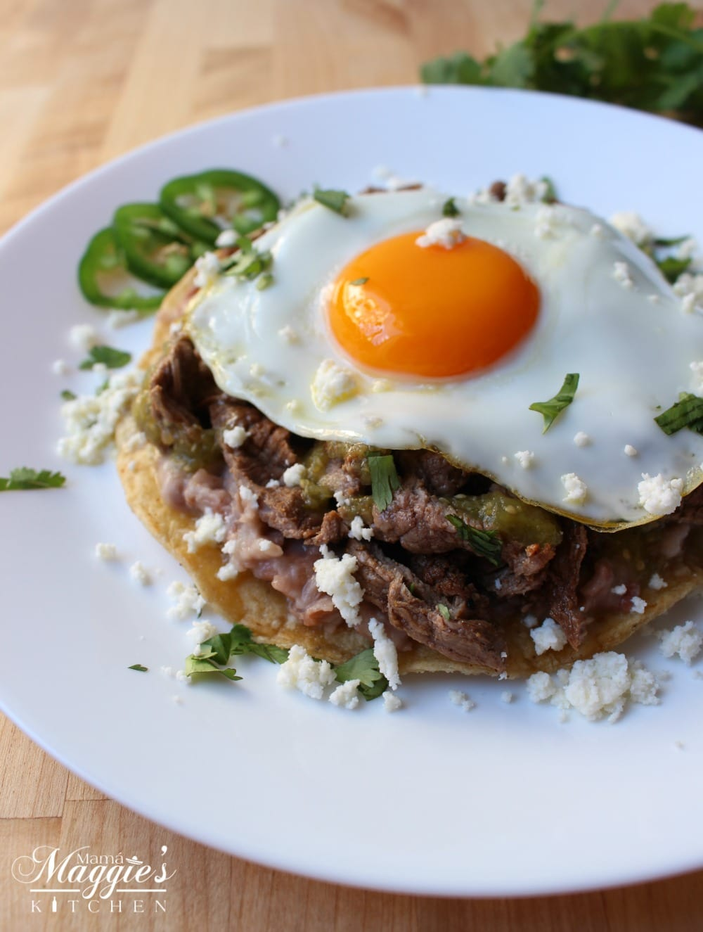 Huevos Rancheros con Bistec, Steak Huevos Rancheros, on a white plate sprinkled with queso fresco and chopped cilantro.