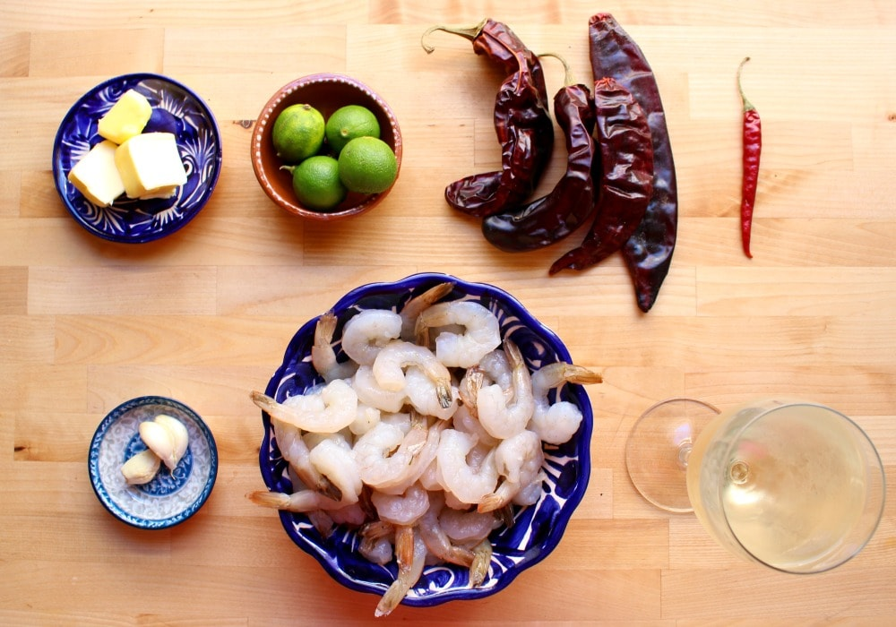 Ingredients for Camarones al Ajillo on a wooden cutting board.
