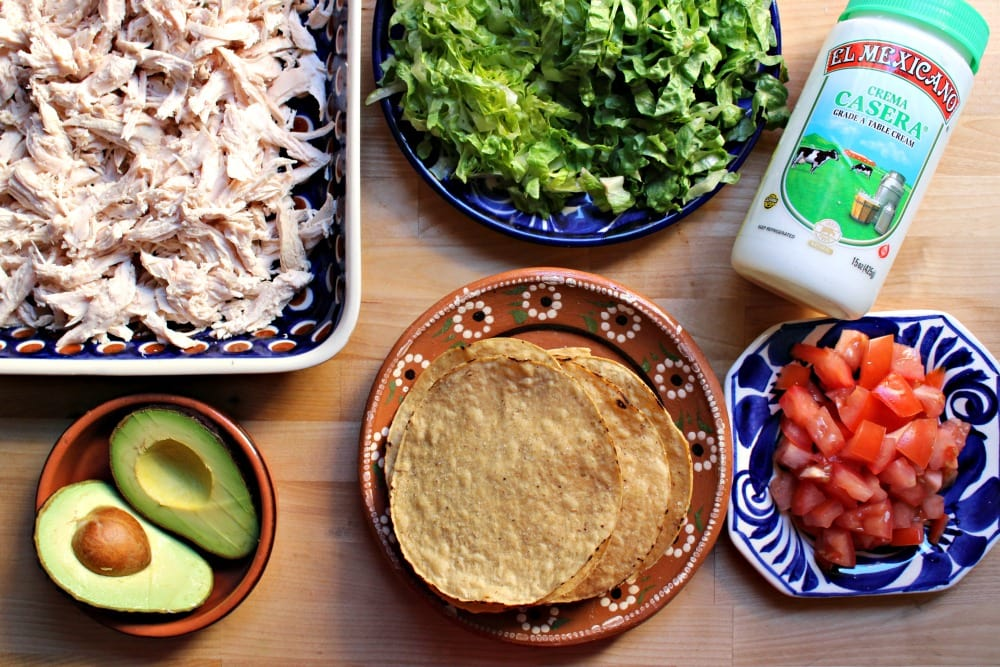 Ingredients for chicken tostadas on a wooden surface - tostadas, tomatoes, lettuce, crema mexicana, shredded chicken, avocado.