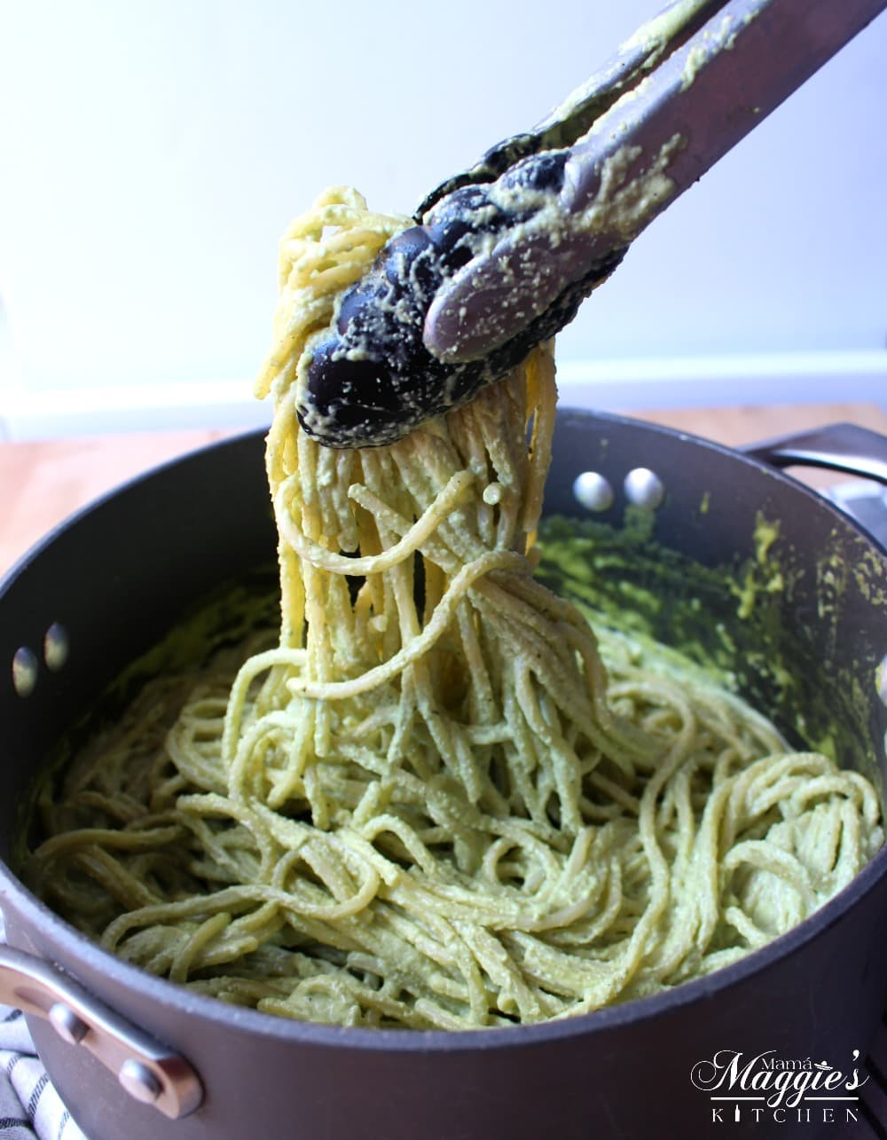 Tongs lifting spaghetti that has been mixed with the creamy poblano sauce.