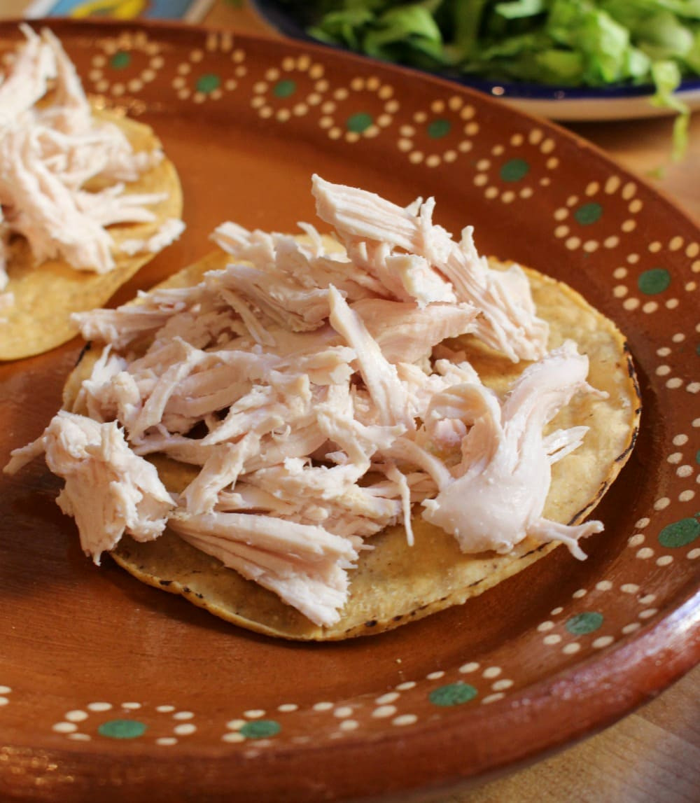 Shredded chicken on top of a tostada on a decorative Mexican clay plate.