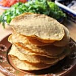 A large stack of tostadas on a decorative Mexican clay plate.