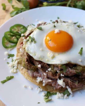 Steak Huevos Rancheros, Huevos Rancheros con Bistec, topped with cilantro and queso fresco.