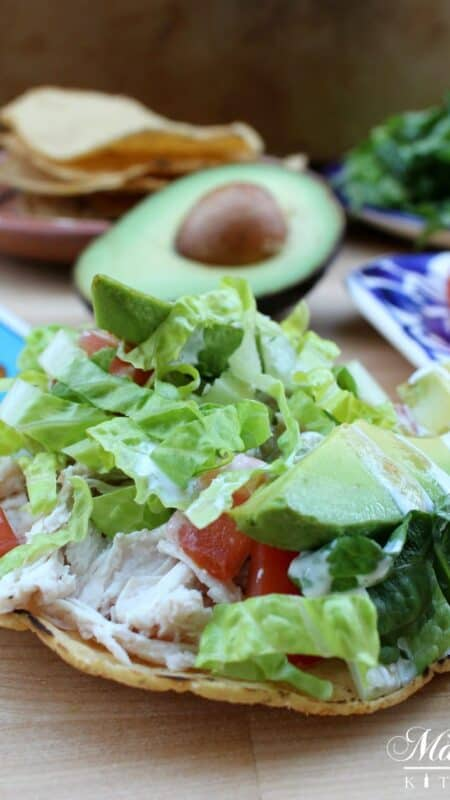 Tostadas de Pollo (Chicken Tostadas) in front of half an avocado, lettuce and tomatoes.
