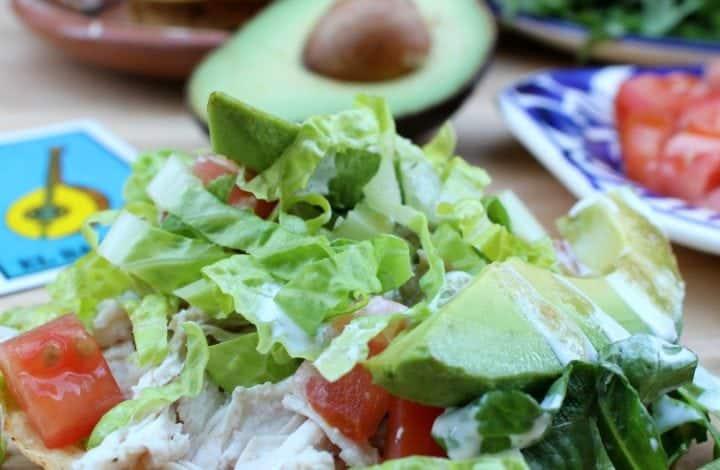 Tostadas de Pollo (Chicken Tostadas) in front of half an avocado, lettuce and tomatoes.