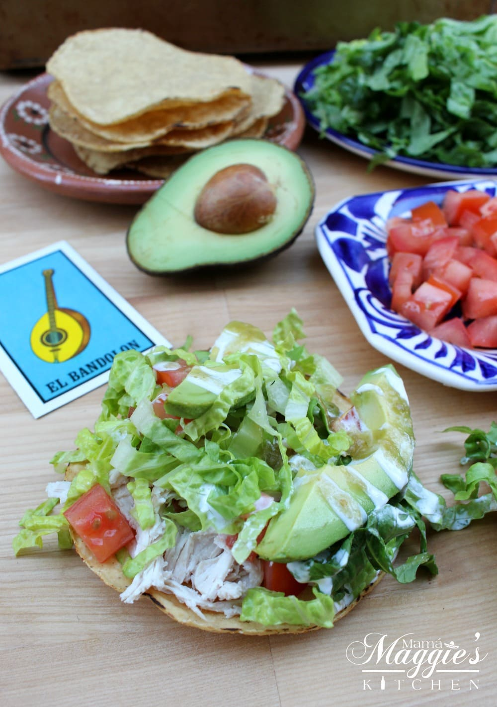 Tostadas de Pollo (Chicken Tostada) surrounded by its ingredient and Loteria cards.