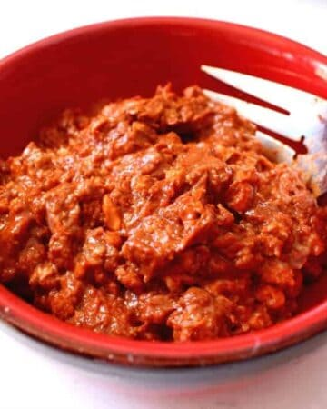Mexican chorizo in a red bowl with a fork on the side.