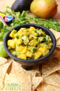 Avocado Mango Salsa in a serving bowl surrounded by chips and the ingredients.