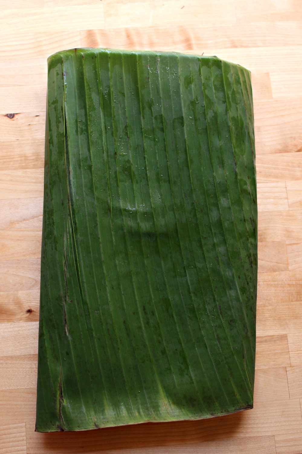 A large piece of banana leaf folded on a wooden surface.