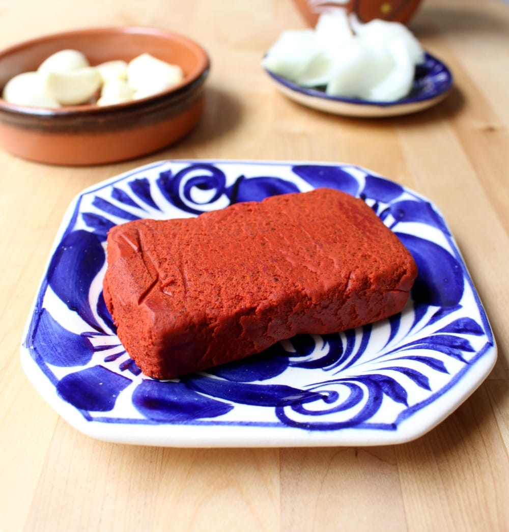 Red achiote Paste on a blue plate.