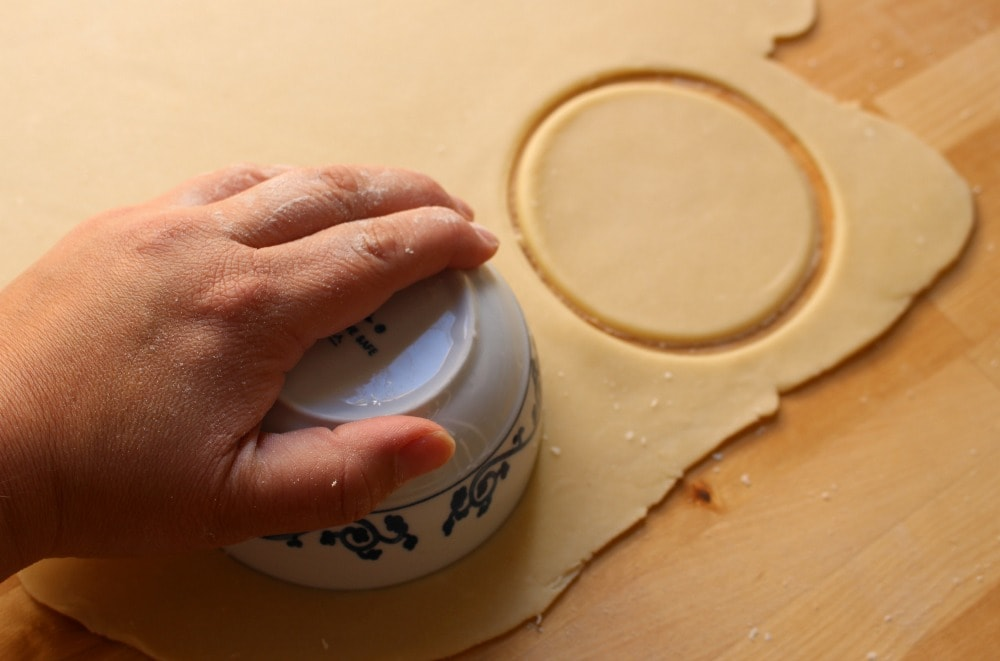 Hand cutting out circles from rolled out dough.