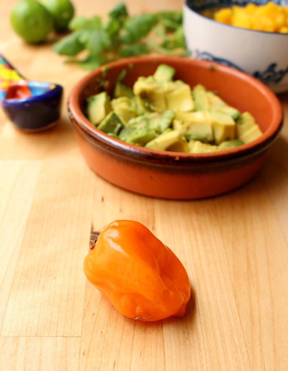 A habanero pepper in front of the ingredients for Avocado Mango Salsa
