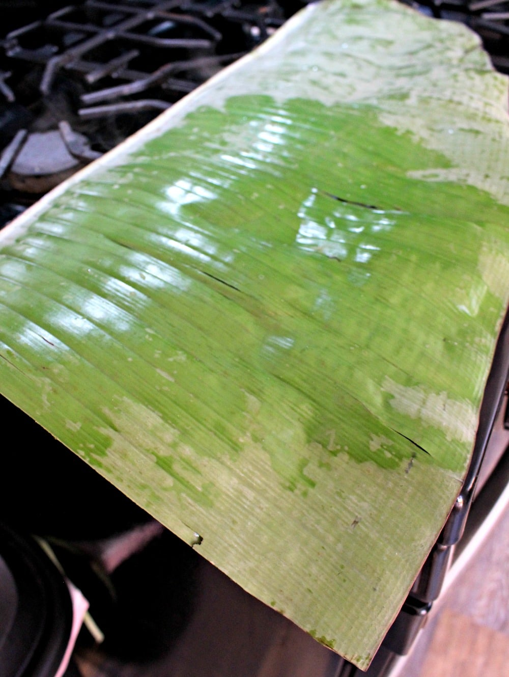 Banana leaves heating up on a gas stove.