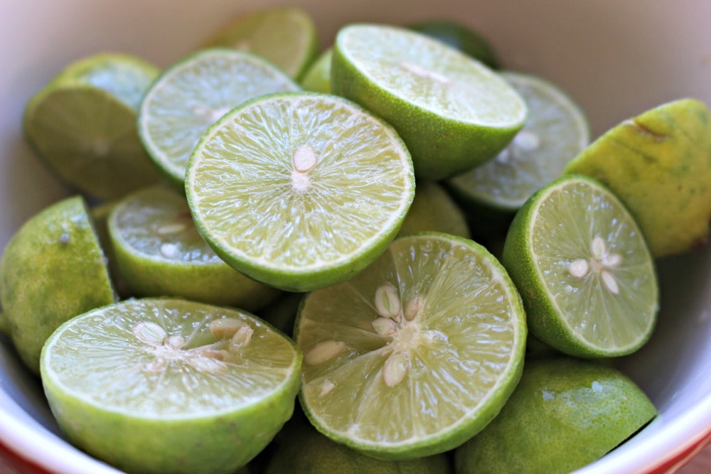 Key limes halved in a white bowl.