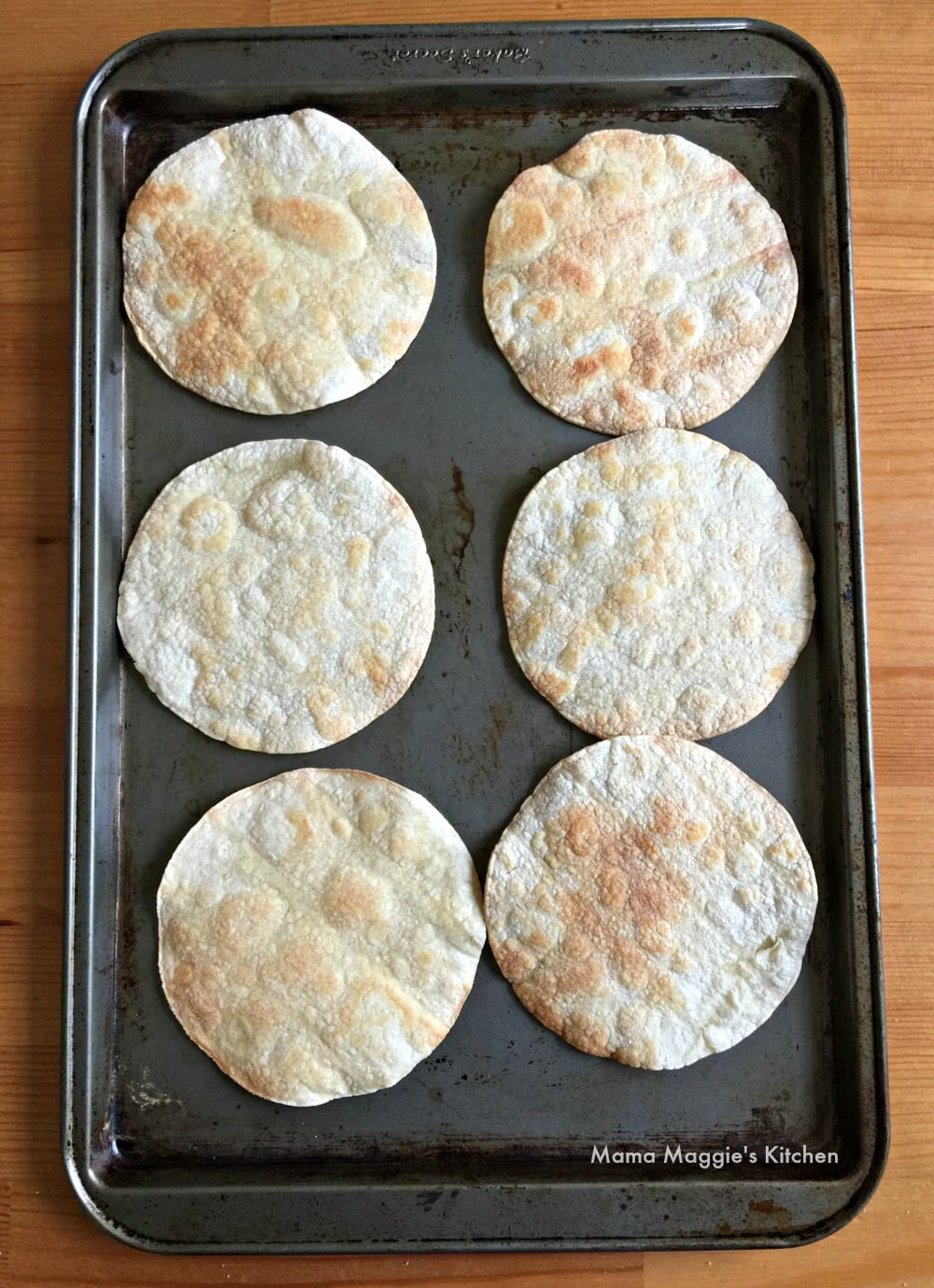 Corn tortillas baking on a cookie sheet.