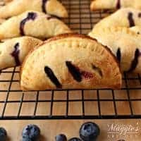 Blueberry Empanadas (or Blueberry Handpies) on a cooling rack surrounded by fresh blueberries.