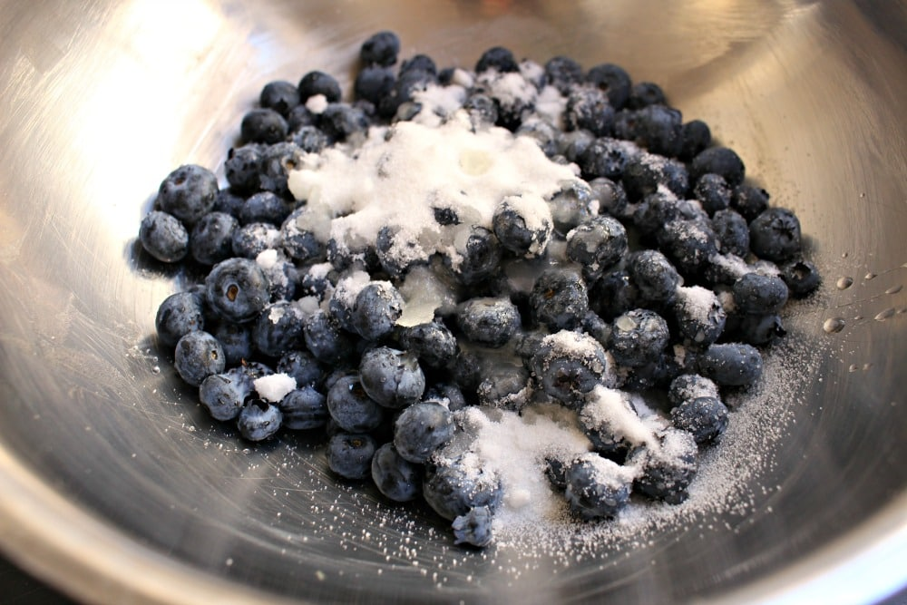 Fresh blueberries mixed with sugar in a metal bowl.