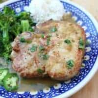 Salsa Verde Pork Chops on a blue plate served next to white rice and green broccoli.