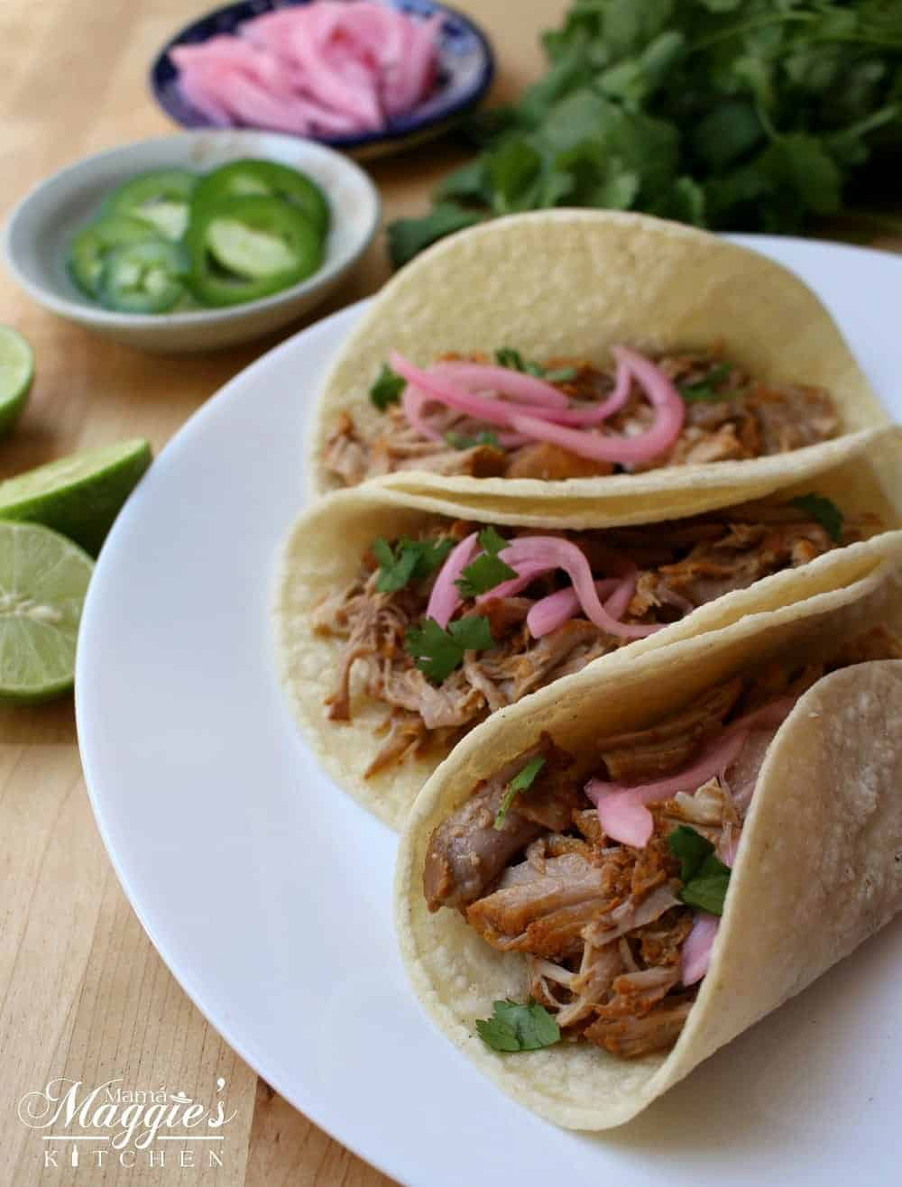 Cochinita Pibil tacos are to die for. Incredibly tender meat topped with chopped cilantro and cebolla en escabeche (pickled red onions). Each bite is heavenly. Recipe with Video and step-by-step pictures. By Mama Maggie's Kitchen