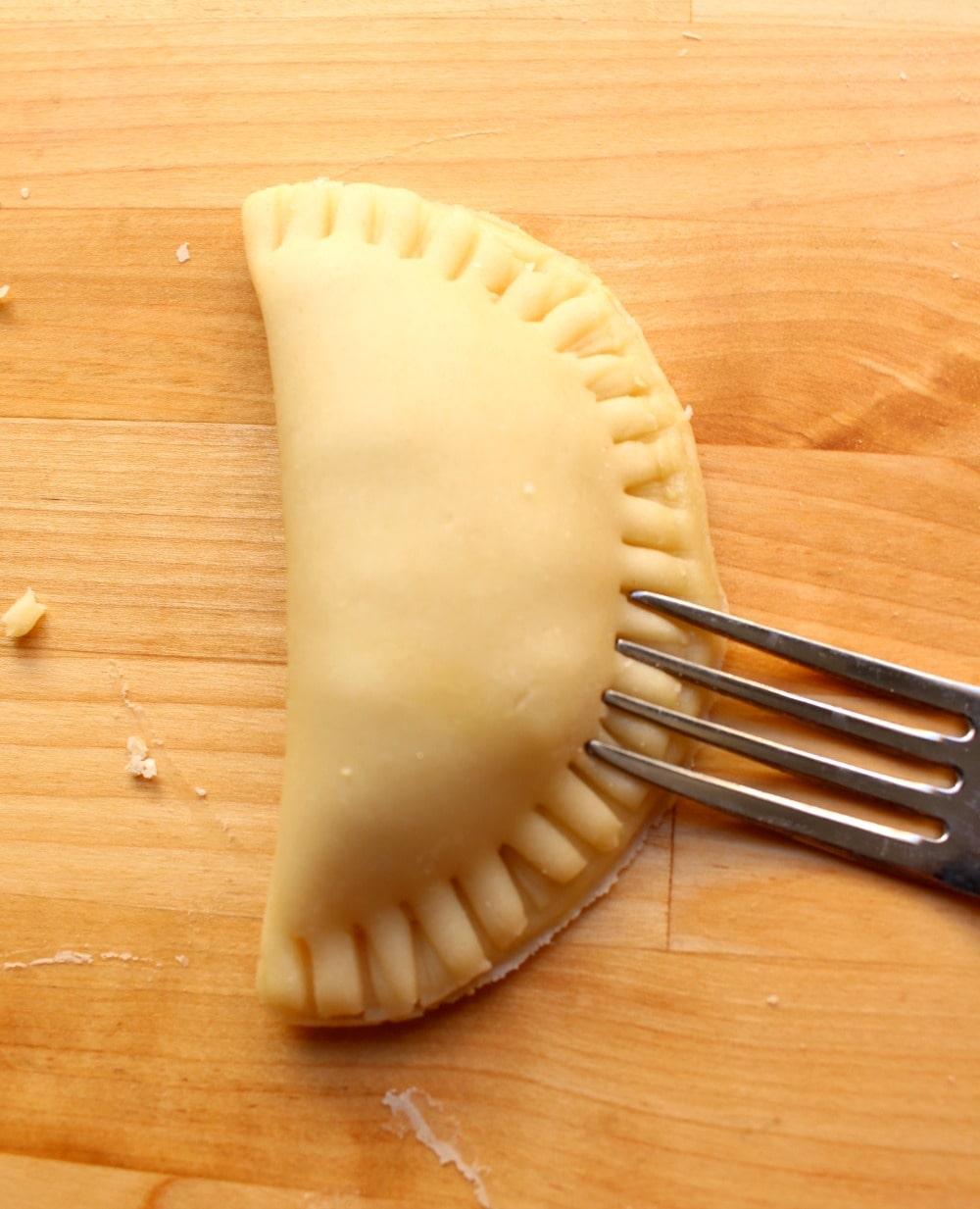 A fork sealing the edges of an empanada.