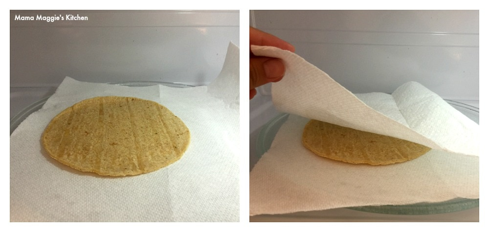 A corn tortilla between two paper towels in a microwave.
