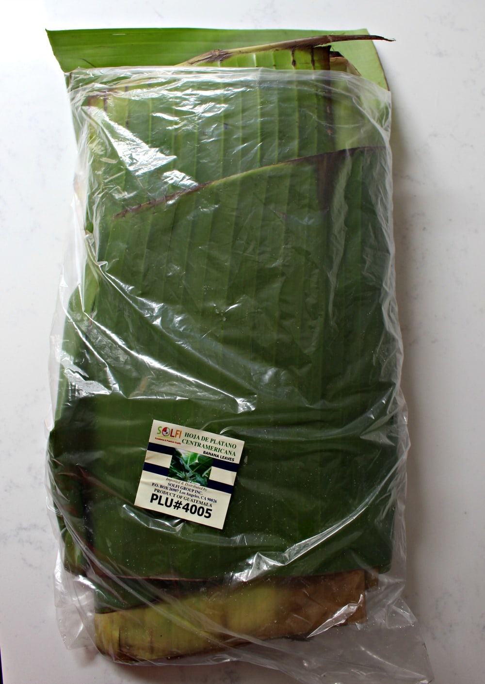 A package of banana leaves on a white granite countertop.