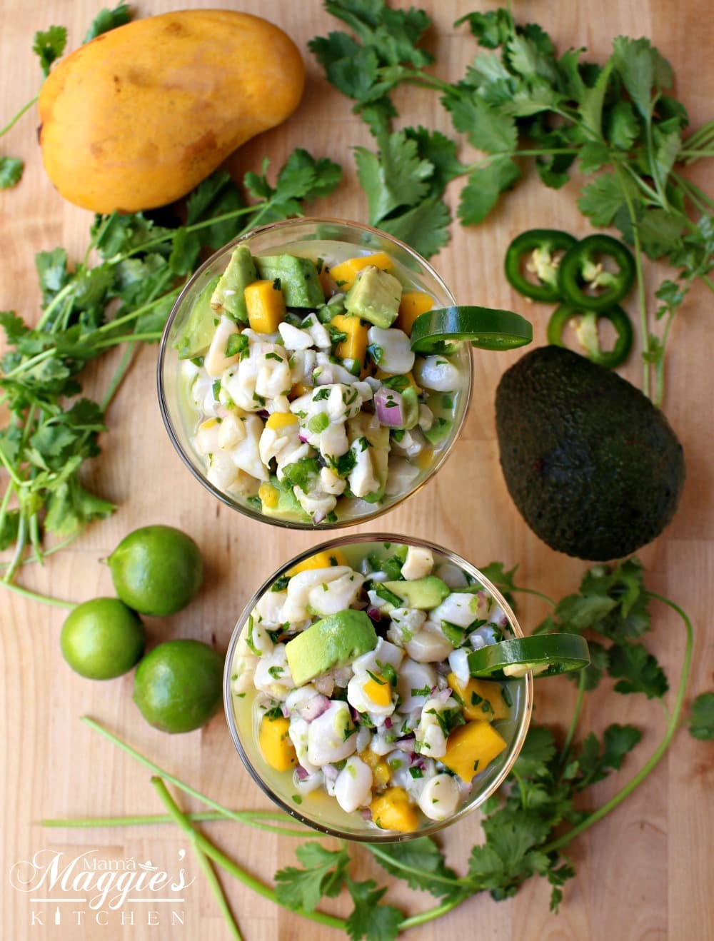Two champagne glasses filled with scallop ceviche surrounded by cilantro, lime, avocado, and mango.