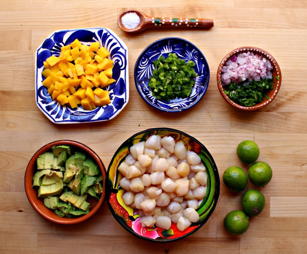 The ingredients for scallop ceviche laid out on a wooden surface.