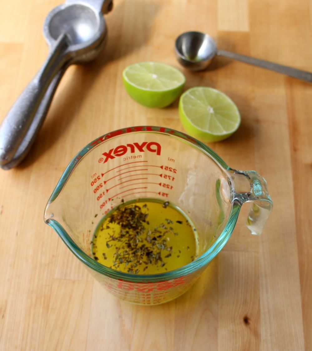 Measuring cup with lime vinaigrette inside.