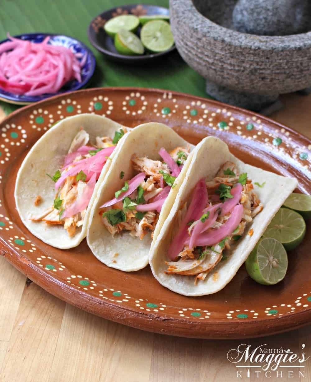 Pollo Pibili tacos on a decorative clay plate topped with red pickled onions.
